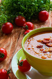 Tomato soup with smoked sausage, tomatoes and lentil. Soup: tomato soup with smoked sausage, tomatoes and lentil. Green bowl on wooden table. Small cherry Stock Photography