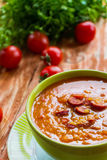 Tomato soup with smoked sausage, tomatoes and lentil. Soup: tomato soup with smoked sausage, tomatoes and lentil. Green bowl on wooden table. Small cherry Stock Photos
