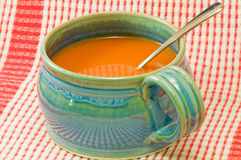 Tomato soup in soup mug. A bowl of hot, delicious tomato soup in a blue soup mug or cup on a red plaid background Stock Images