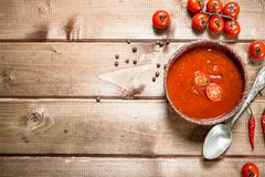 Tomato soup with spices and hot chili peppers. On a wooden background stock photos