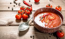 Tomato soup with spices and hot chili peppers. On a wooden background stock image