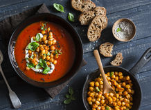 Tomato soup with spicy fried chickpeas on a dark wooden table, top view. Healthy vegetarian food. Concept Stock Photos