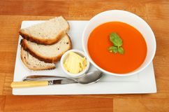 Tomato soup on a tabletop. Tomato soup in a bowl with bread and butter on a rectangular plate on a wooden tabletop Royalty Free Stock Images
