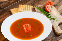 Tomato soup with toast and chive. On wood plate stock images