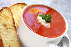 Tomato Soup with Toasted Turkish Bread. Tomato soup with toasted Turkish herb bread, in a white bowl Royalty Free Stock Images
