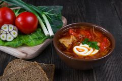 Tomato soup . Traditional  Ukrainian beetroot and tomato soup - borsch in clay pot with sour cream, garlic, herbs and bread. On dark wooden background Stock Photos