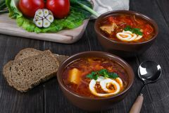 Tomato soup . Traditional  Ukrainian beetroot and tomato soup - borsch in clay pot with sour cream, garlic, herbs and bread. On dark wooden background Royalty Free Stock Image