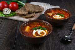 Tomato soup . Traditional  Ukrainian beetroot and tomato soup - borsch in clay pot with sour cream, garlic, herbs and bread. On dark wooden background Stock Image