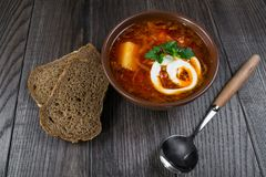 Tomato soup . Traditional  Ukrainian beetroot and tomato soup - borsch in clay pot with sour cream, herbs and bread. On dark wooden background Royalty Free Stock Photography