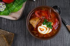 Tomato soup . Traditional  Ukrainian beetroot and tomato soup - borsch in clay pot with sour cream, herbs and bread. On dark wooden background Royalty Free Stock Image