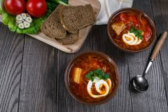 Tomato soup . Traditional  Ukrainian beetroot and tomato soup - borsch in clay pot with sour cream, herbs and bread. On dark wooden background Stock Images