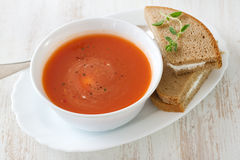 Tomato soup in white bowl with sandwich Stock Photo