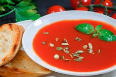 Tomato soup in a white plate with Basil stock photos