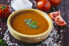 Tomato soup in a wooden bowl royalty free stock photo