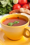 Tomato soup in yellow cup with ingredients Stock Photo