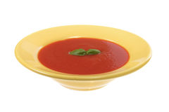 Tomato soup in yellow plate Stock Images