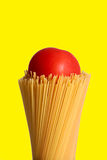 Tomato on spaghetti. A tomato sits on top of a bunch of dried spaghetti noodles Royalty Free Stock Image