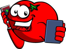 Tomato speaking on a smartphone while reading a tablet Royalty Free Stock Photo