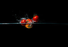 Tomato splash. Tomato dropping in water on black background Stock Photography
