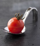 Tomato on spoon Stock Photo