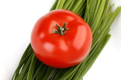 Tomato and spring onion. On white plate Royalty Free Stock Photography