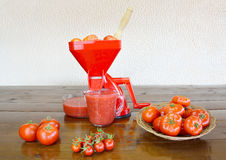 Tomato strainer and fresh tomatoes Stock Images