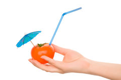 Tomato with straw and cocktail umbrella royalty free stock photos