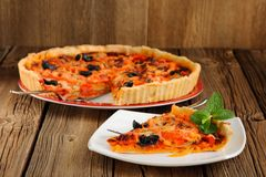 Tomato tart with olives on wooden background Royalty Free Stock Photography