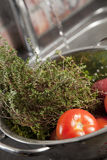 Tomato Thyme Preparation. Cooking fresh ingredients in stainless steel pasta strainer with tap running in background Royalty Free Stock Image