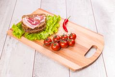 Tomato, toasts, meat and salad on wooden table Royalty Free Stock Photo