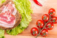Tomato, toasts, meat and salad on wooden table Royalty Free Stock Image