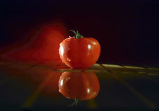 Tomato in unique lighting. A still life view of a ripe red tomato with unique and beautiful lighting effects Stock Images