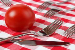 Tomato with utensils Royalty Free Stock Image
