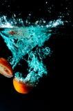 Tomato water splash on black background Stock Images