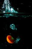 Tomato water splash on black background. Fresh tomato water splash on black background Royalty Free Stock Photography