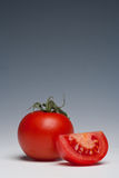 Tomato whole and sliced. On a plain background Royalty Free Stock Photo