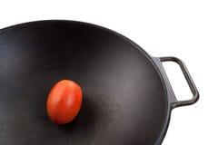 Tomato in Wok. A fresh roma tomato in a black cast iron wok Stock Photos