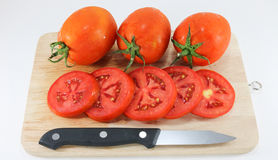 Tomato on wood chopping block with knife white background isolated Royalty Free Stock Images