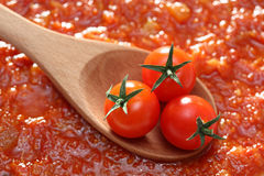 Tomato in a wooden spoon. Tomatoes in a wooden spoon on tomato sauce background. Close-up Stock Images