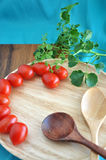 Tomato on wooden tray and spoons Stock Photo