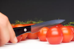 Tomatocutter. Hand with a black knife cuts a tomato Royalty Free Stock Photography