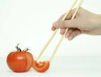 Tomatoe and chopsticks. Royalty Free Stock Images