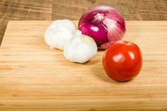 Tomatoe garlic cloves and red onion. Tomato with cloves of garlic and a red onion Royalty Free Stock Images