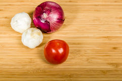 Tomatoe garlic cloves and red onion. Tomato with cloves of garlic and a red onion Royalty Free Stock Photos