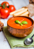 Tomatoe soup with bread sticks and basil on wooden background Stock Photo