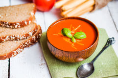 Tomatoe soup with bread sticks and basil on wooden background Royalty Free Stock Images