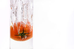 Tomatoe splash. Ing on water, inside a glass container Royalty Free Stock Image