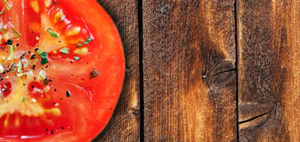 Tomatoe on wood. Red tomatoe with herbs on weathered wood background Stock Photos