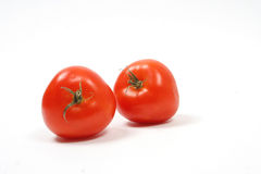 Tomatoes. Two fresh tomatoes isolated on white background waiting to be prepared for salad Royalty Free Stock Photography