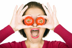 Tomatoes. Young, surprised looking lady looking 'through' two tomatoes Royalty Free Stock Images